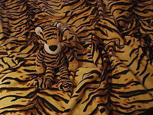 Plüschtiger auf einer Fleecedecke mit Tigermuster